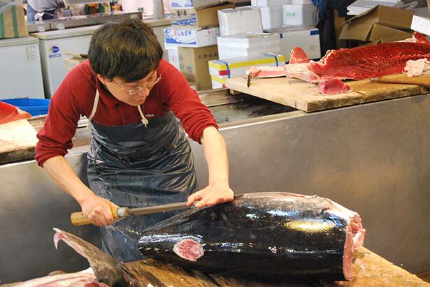 Un pescadero cortando su mercancía en el mercado de Tsukiji