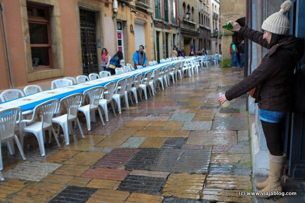 Una joven escancia sidra bajo la lluvia en la Comida en la Calle en  Avilés