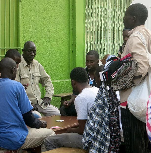 Gente jugando a cartas frente al mercado de Kermel