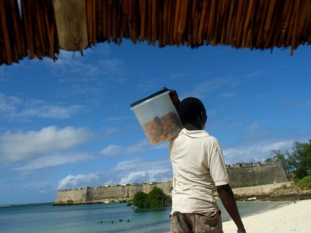 El vendedor de dulces en la playa. A lo lejos, la fortaleza de San Sebastián