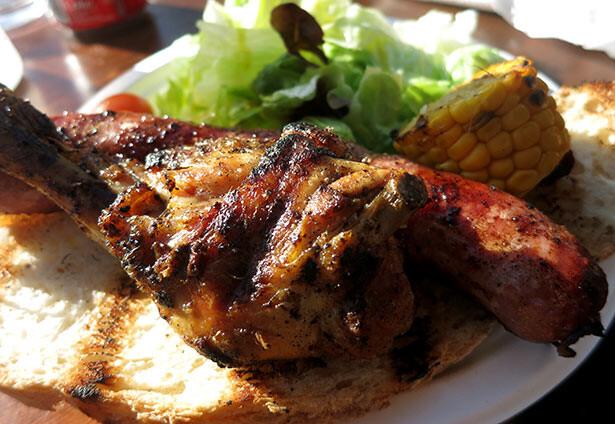 El plato principal consiste en butifarra, pollo, maíz y ensalada