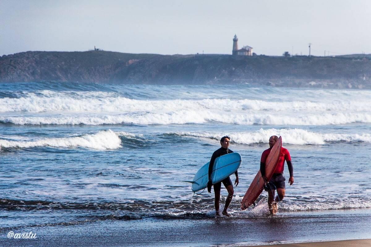 Surferos saliendo del agua en la playa de Salinas (Asturias)